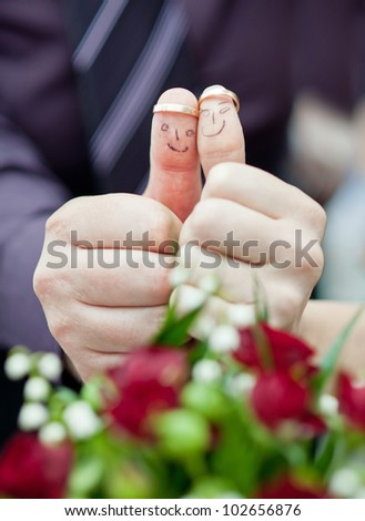 wedding rings on her fingers painted with the bride and groom