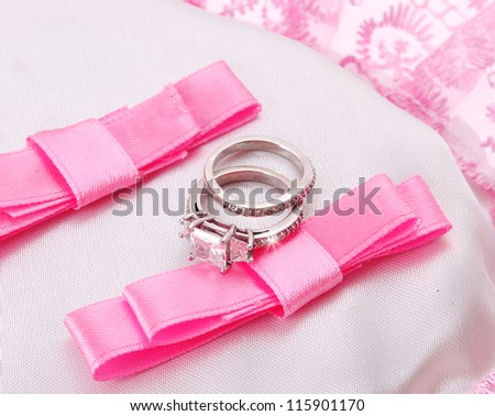 wedding rings on pink bow isolated on white