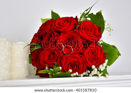 Wedding rings on red roses wedding bouquet #401587810