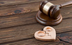 Wedding rings on the figure of a broken heart from a tree, hammer of a judge on a wooden background. Divorce divorce proceedings