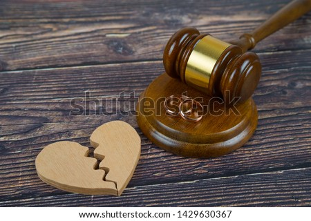 Wedding rings on the figure of a broken heart from a tree, hammer of a judge on a wooden background. Divorce divorce proceedings #1429630367