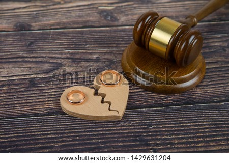 Wedding rings on the figure of a broken heart from a tree, hammer of a judge on a wooden background. Divorce divorce proceedings #1429631204
