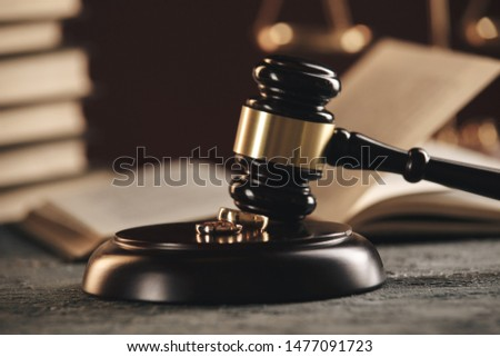 Wedding rings on the figure of a broken heart from a tree, hammer of a judge on a wooden background. Divorce divorce proceedings #1477091723