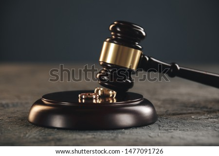 Wedding rings on the figure of a broken heart from a tree, hammer of a judge on a wooden background. Divorce divorce proceedings #1477091726