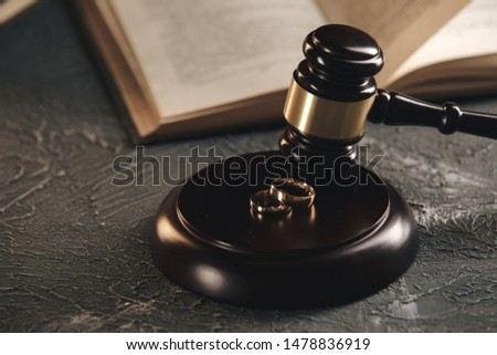 Wedding rings on the figure of a broken heart from a tree, hammer of a judge on a wooden background. Divorce divorce proceedings #1478836919