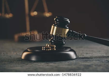 Wedding rings on the figure of a broken heart from a tree, hammer of a judge on a wooden background. Divorce divorce proceedings #1478836922