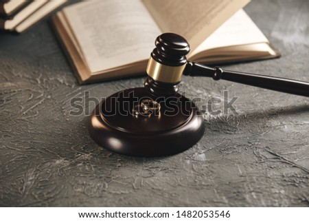 Wedding rings on the figure of a broken heart from a tree, hammer of a judge on a wooden background. Divorce divorce proceedings #1482053546