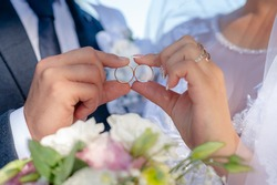 Wedding rings on the hands of the newlyweds on their wedding day. Family bonds. Family and marriage concept