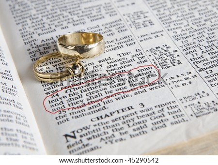 stock photo Wedding rings place on an open Bible to a verse in the book
