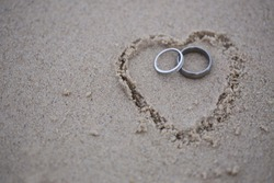 Wedding rings put in the sand drawing shape heart. Wedding rings for the bridal. Wedding diamond rings.