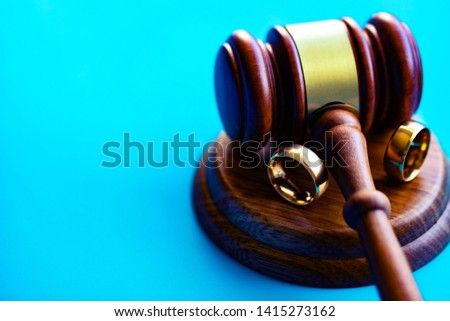 Wedding rings separated by judge hammer. Court decision on divorce concept. #1415273162