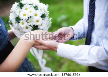 Wedding rings, wedding day. Wedding couple. He put an engagement ring on her. bridegroom puts the ring on the bride in nature. the moment when the groom puts the ring on the bride. #1376015936