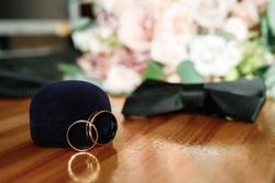 Wedding rings with bridegroom butterfly on the wooden floor. Weddig card