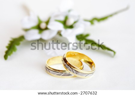 stock photo Wedding rings with small flower on white background