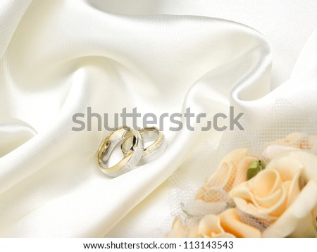 Wedding rings, yellow roses and white silk