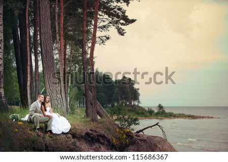 Wedding romance - bride and groom sitting at the coast of the Sea.