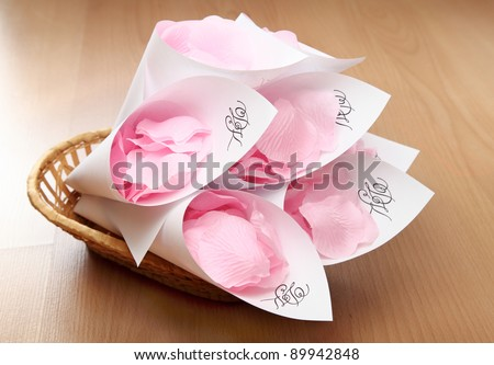 Wedding rose petals wrapped in paper with initials of bride and groom - stock photo