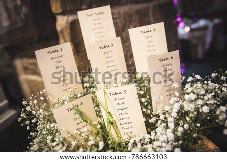 wedding seating plan displayed on cards with a bunch of white flowers
