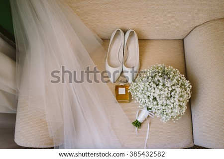 wedding set of bridal bouquet, white shoes, perfume and veil on the beige armchair