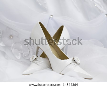 wedding shoes on  white bridal dress - stock photo