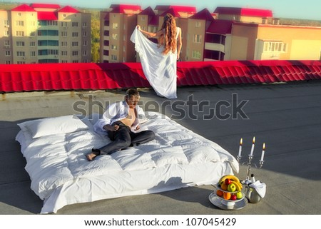 Wedding shot of bride and groom next to a stylish bed on roof