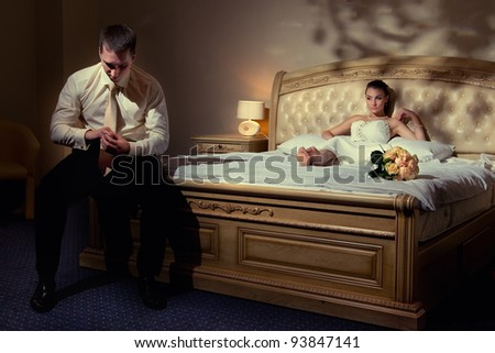 Wedding shot of bride and groom sitting on a stylish bed