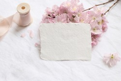 Wedding spring styled stock photo. Feminine desktop mockup scene with pink blossoming Japanese cherry tree branch and blank paper greeting card on white linen table background. Flat lay, top view.
