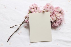 Wedding spring styled stock photo. Feminine desktop mockup scene with pink blossoming Japanese cherry tree branches and blank paper greeting card on white linen table background. Flat lay, top view.
