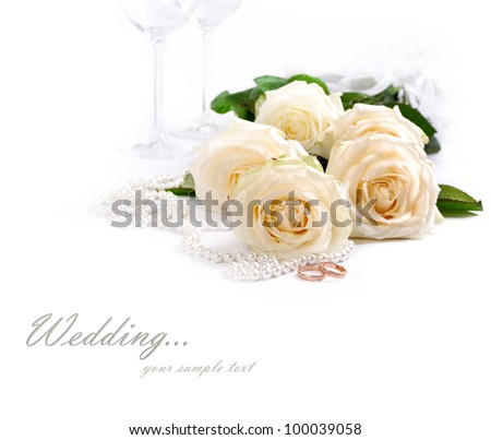 Wedding still life with white roses, golden rings an pearls