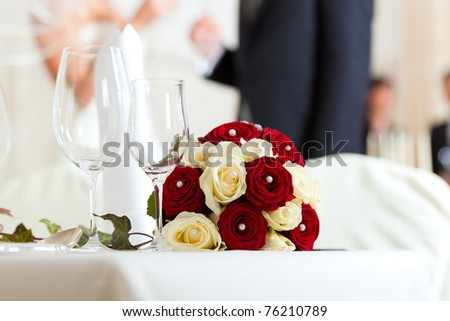 Wedding table at a wedding feast decorated with bridal bouquet