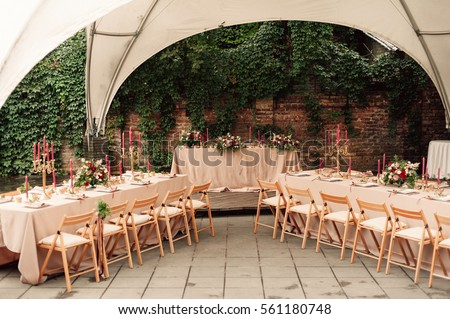 Wedding table decor with red flowers and plates  #561180748