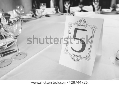 Wedding table with the sign number five, pictures in BW