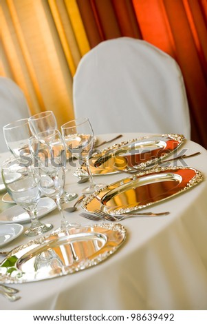 wedding table with white tablecloth and silver platters set for fine dining
