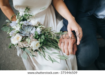 Wedding. The girl in a white dress and a guy in a suit sitting on a wooden chair, and are holding a beautiful bouquet of white, blue, pink flowers and greenery, decorated with silk ribbon #375446509