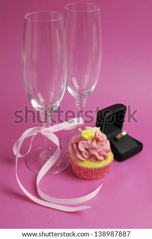 Wedding theme bridal pair of champagne flute glasses with pink cupcake and wedding ring in black jewelry box against a pink background. Vertical.