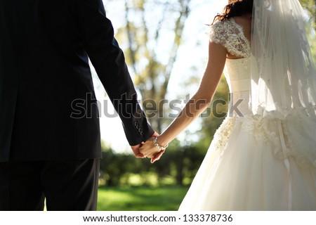 Shutterstock wedding theme, holding hands newlyweds