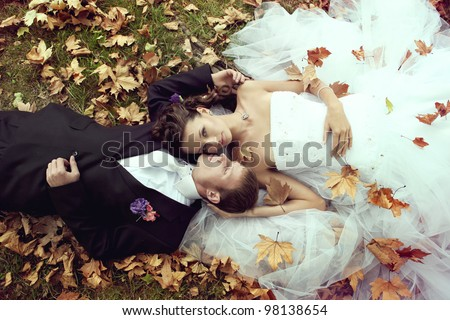 wedding theme, the bride and groom are in the maple leaves on grass