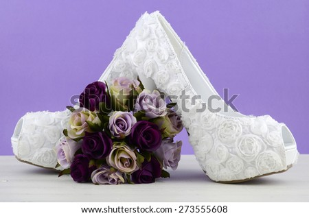 Wedding theme white floral bridal shoes with flowers on shabby chic white table and purple background.