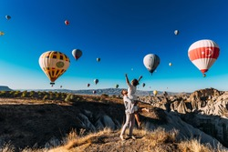 Wedding travel. Honeymoon trip. Couple in love among balloons. A guy proposes to a girl. Couple in love in Cappadocia. Couple in Turkey.  Man and woman traveling. Festival of balloons. Tourists