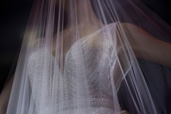Wedding veil on a mannequin. Transparent white cloth on a plastic mannequin. Demonstration of the wedding accessory. Shooting in the dark with lightweight fabric.