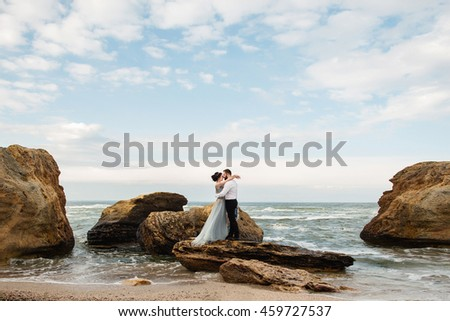 Wedding. Wedding by the sea. Young couple in love, bearded groom hugs a bride in a wedding dress at the ocean. Standing on cliffs around the sea and the rocks near the place of the wedding ceremony.