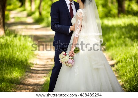 Wedding. Wedding day. Beautiful bride and elegant groom walking after wedding ceremony. Luxury bridal dress and bouquet of flowers. Bride and groom at wedding day #468485294