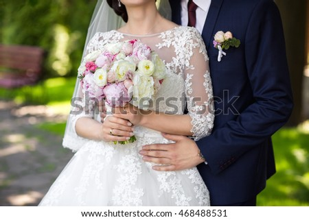 Wedding. Wedding day. Beautiful bride and elegant groom walking after wedding ceremony. Luxury bridal dress and bouquet of flowers. Bride and groom at wedding day #468488531