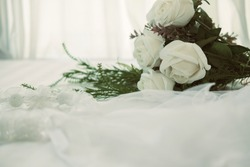 wedding white bridal veil & rose flower bouquet on bed beside see through sheer window curtain