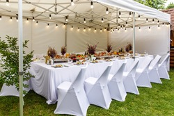 Wedding white tent with white chairs. Banquet hall under a tent for wedding or another catered event dinner