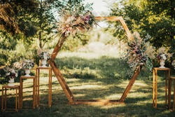 Wedding wooden arch in rustic style decorated with grass hay field color and flowers. Near wooden boxes with flower bouquets. Wooden arch and flower decoration. Wedding ceremony in sunny summer day.