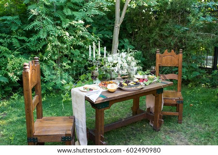 Wedding wooden banquet table. Wooden retro chair. Served table with a glass of red wine, melon, red currants, gooseberry, grilled vegetables - Shutterstock ID 602490980