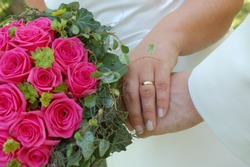 Weddingcouple holding their hands and weddingflowers