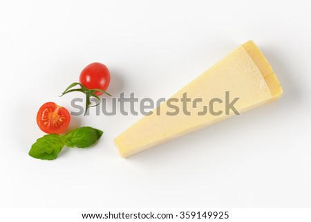 wedge of fresh parmesan cheese and cherry tomatoes on white background