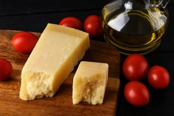 Wedge of italian hard cheese Parmesan or Grana Padano on a brown wood cutting boad, small red tomatoes and olive oil over black wood table. Low key image. Front view.